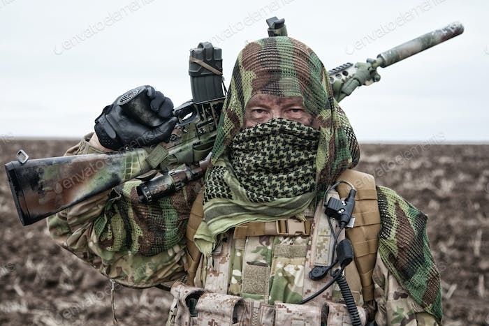 Army sniper standing in field with rifle
