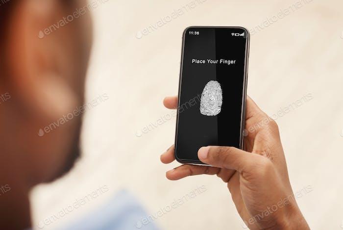 Man holding phone with fingerprint scanning app