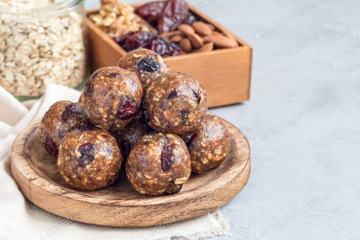 Healthy homemade energy balls on wooden plate, horizontal, copy space