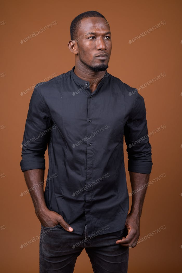 Portrait of handsome African businessman against brown background