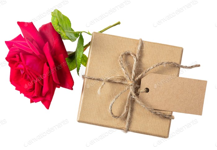 Rose red flower and a gift box with a blank tag on a white background, top view, space for text