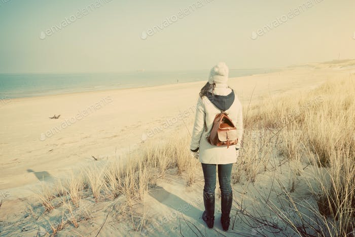 Woman with retro backpack on the beach looking at the sea