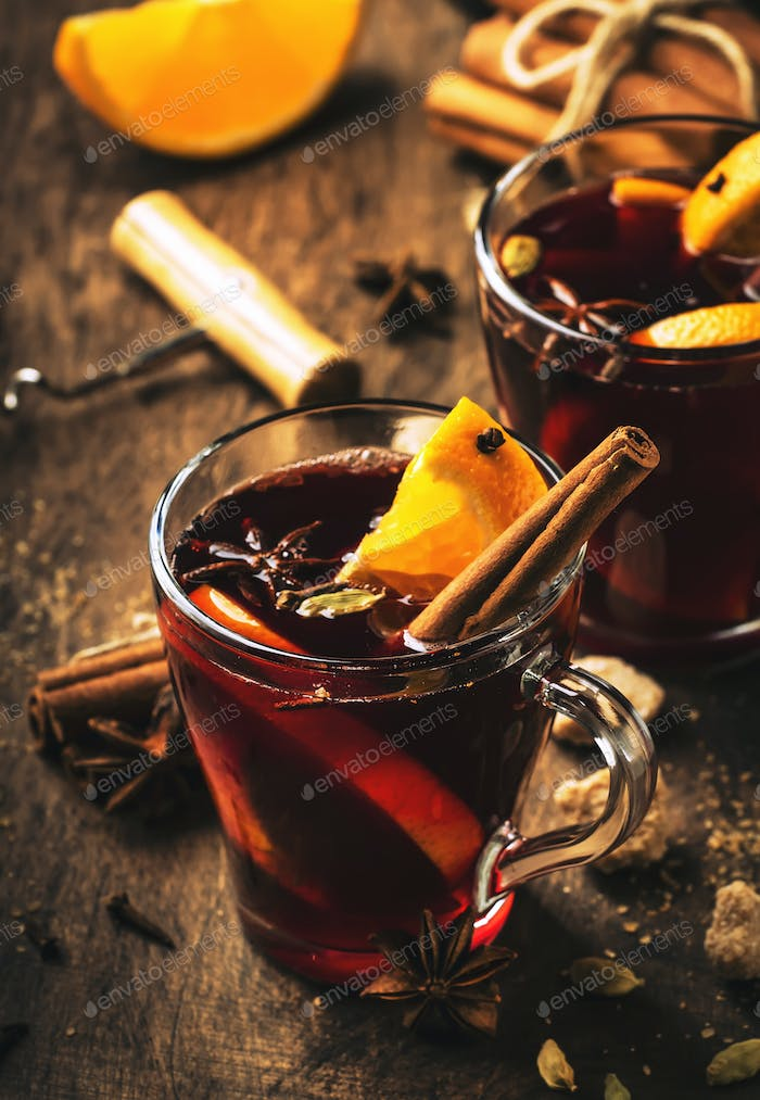 Hot mulled red wine cups with spices and fruits on wooden rustic table