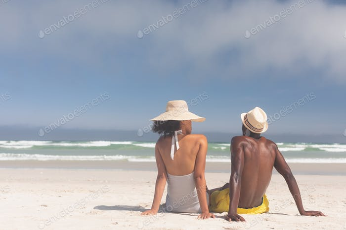 Rear view of Multi-ethnic couple relaxing at beach on a sunny day