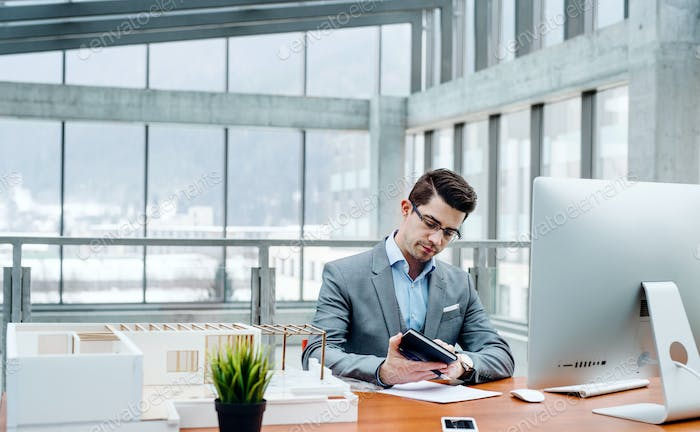 Young businessman or architect with model of a house sitting in office, working.