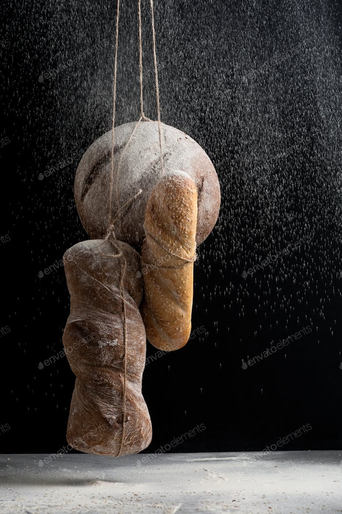 Three kinds of fresh bread in a fog of flour on a black backgrou