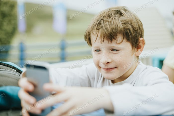 Happy boy playing on a mobile phone