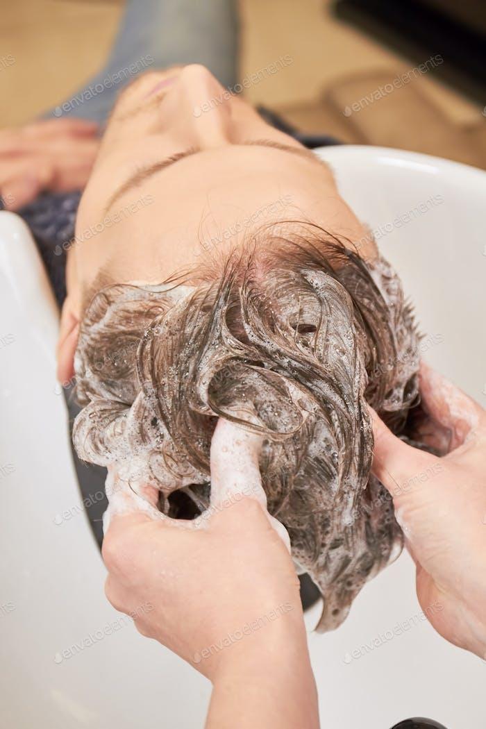 Hands washing hair with shampoo