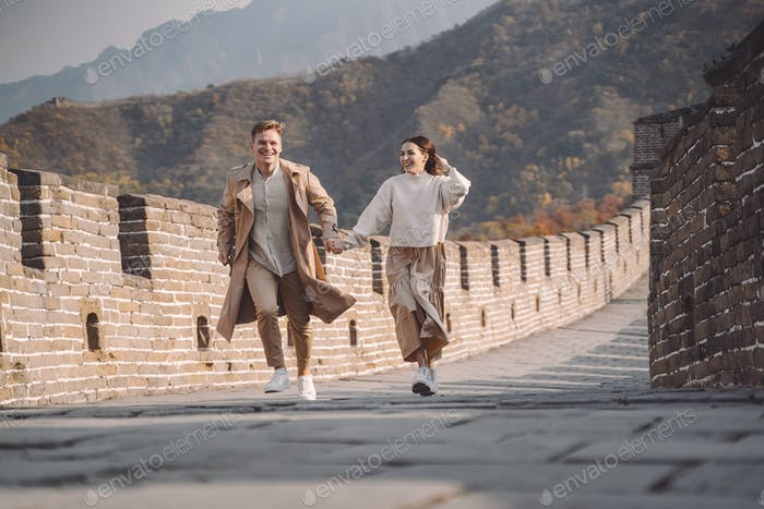 beautiful young couple running and jumping at the Great Wall of China