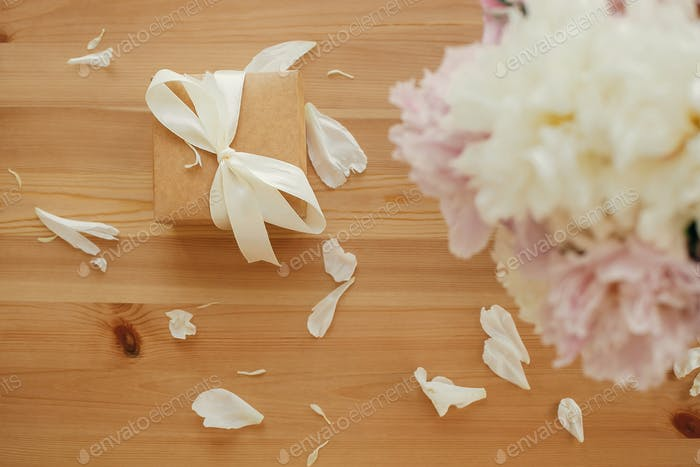Beautiful peonies in vase and gift box on rustic wooden table top view