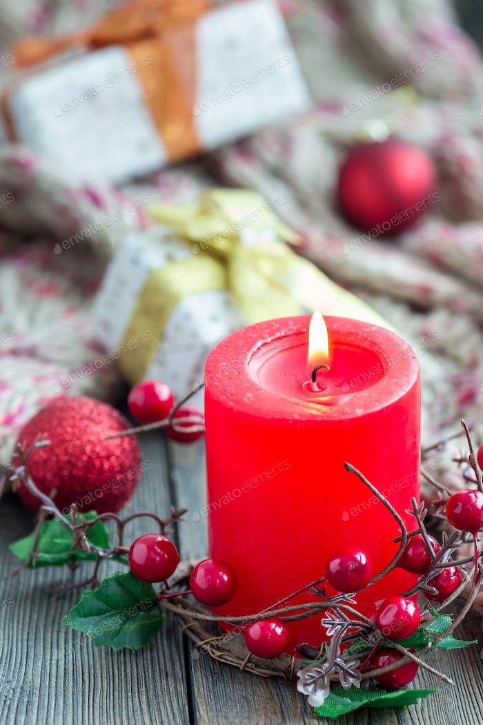 Weihnachtskomposition mit Kerze, Dekorationen und Geschenkboxen auf Holzbrett