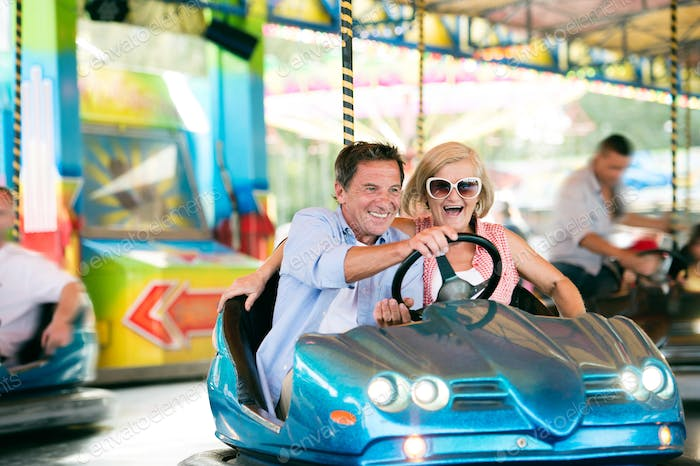 Senior couple in the bumper car at the fun fair