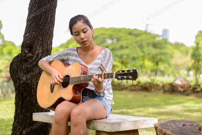 Young beautiful Asian woman playing guitar while sitting at the park