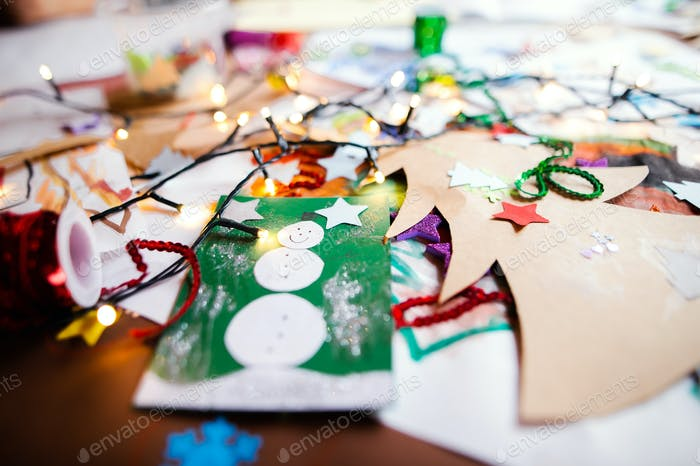 Children's paintings and Christmas paper art and craft on table