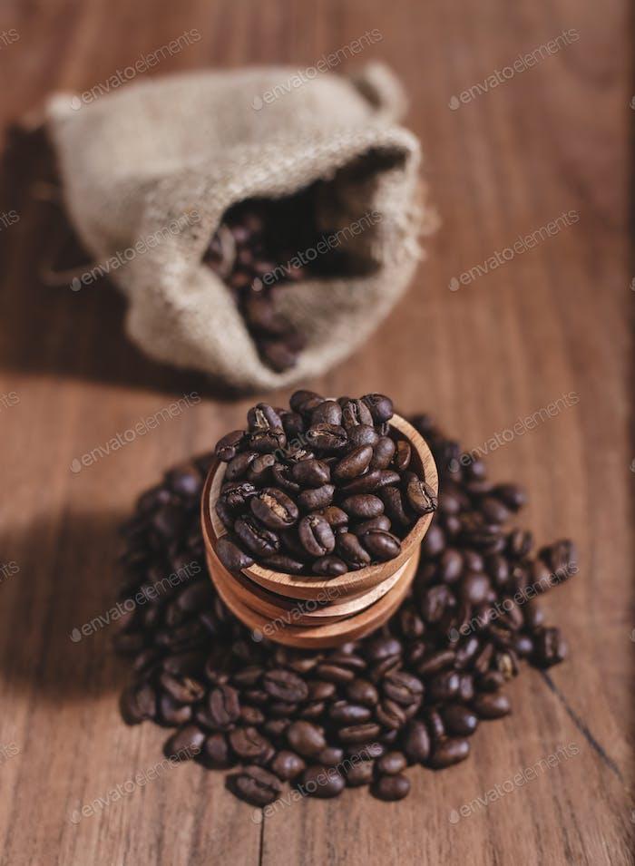 Kaffeebohnen auf Holzuntertasse und Kaffeebeutel
