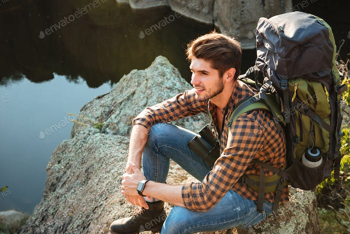 Top view of adventure man sitting on rock