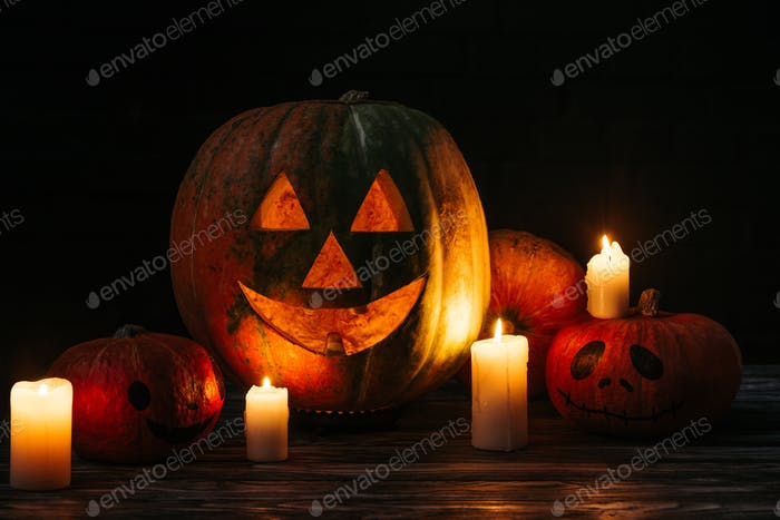 spooky halloween carved pumpkins with candles on wooden table on black background