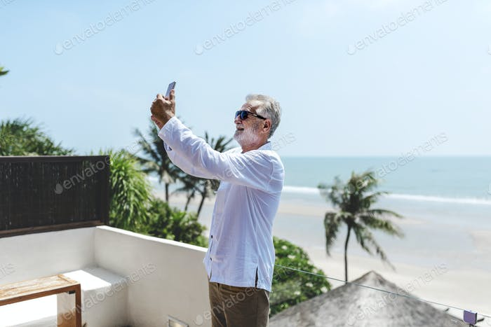 Senior man on vacation taking a selfie