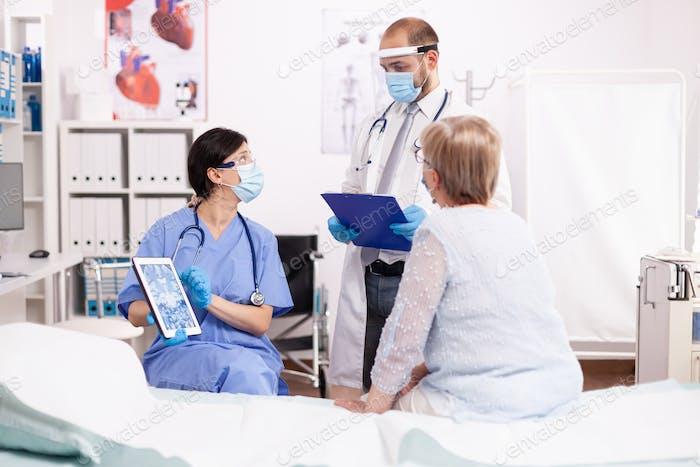 Arzt und Krankenschwester führen Untersuchung eines älteren Patienten durch
