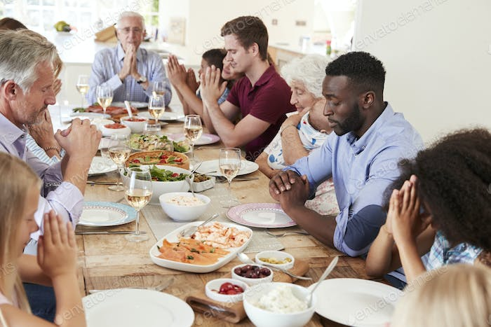 Multi-Generation Family And Friends Around Table Praying Before Meal At Party