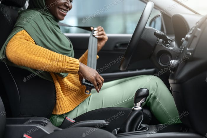 Safety First. Unrecognizable Black Muslim Lady Fasten Seatbelt Before Car Ride
