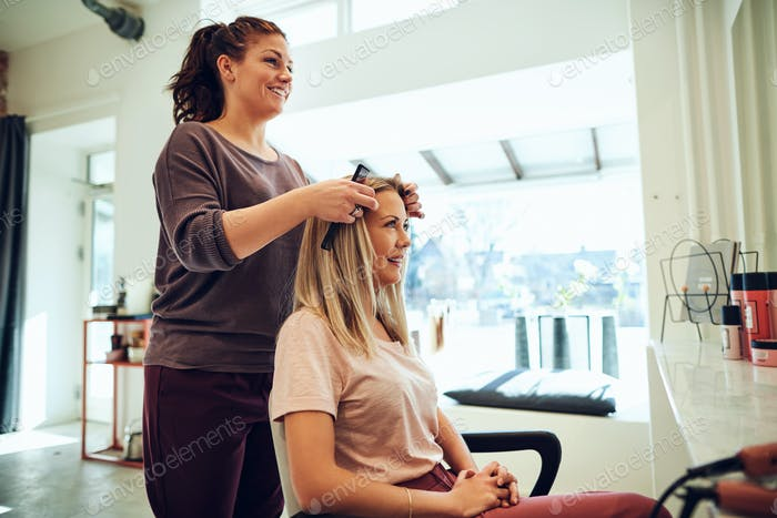 Smiling young woman discussing her hairstyle with a salon stylist