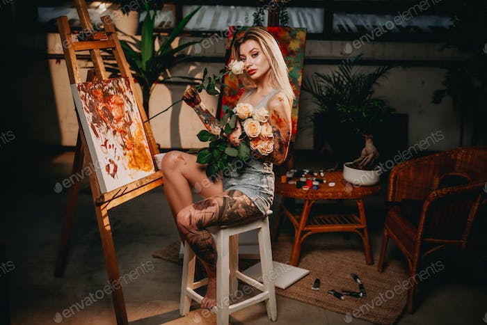 Dark room with artwork and blond haired painter with roses