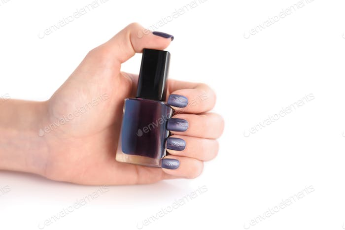 Hand of a woman with dark manicure and nail polish bottle on white background