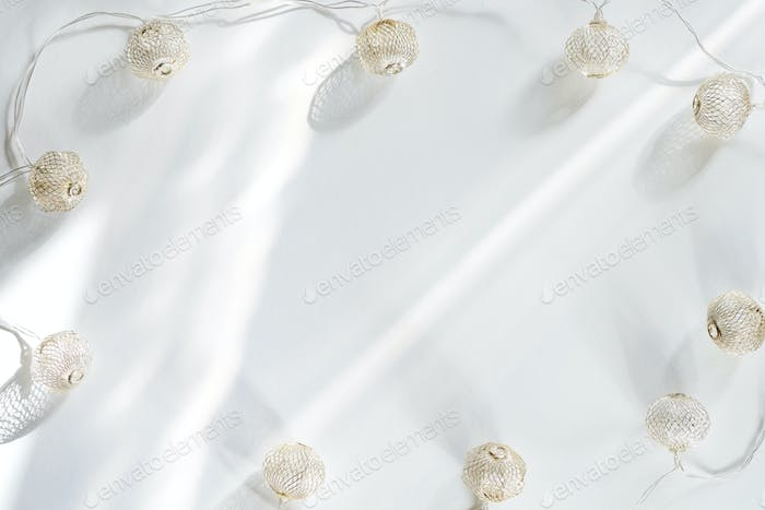 Christmas light balls with sunlight rays on a white background. Flat lay copy space