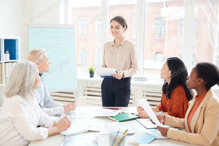 Smiling Woman Giving Presentation at Business Meeting
