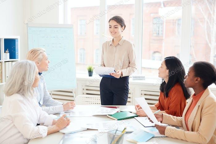 Mujer sonriente dando presentación en reunión de negocios