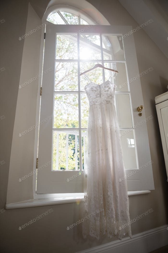 Wedding dress hanging on window