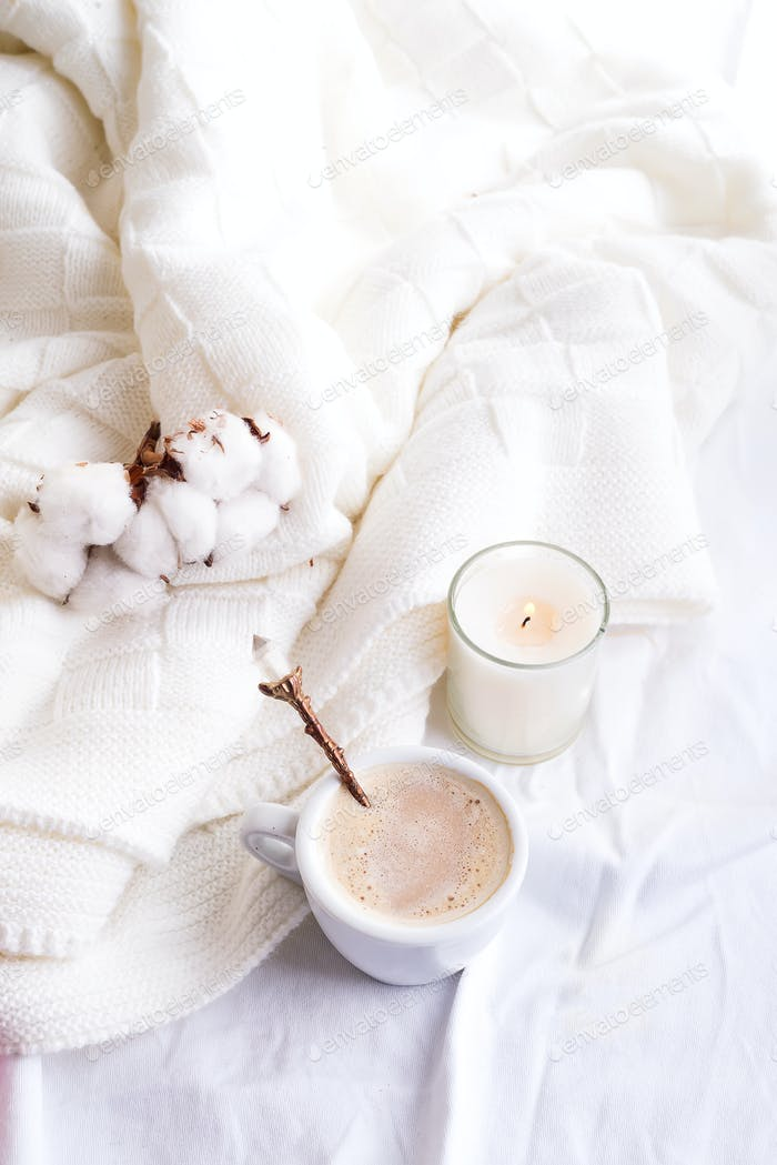 Bedding with a fluffy knitted plaid and cup of coffee, cotton flowers and candle. Cozy day. Flat lay