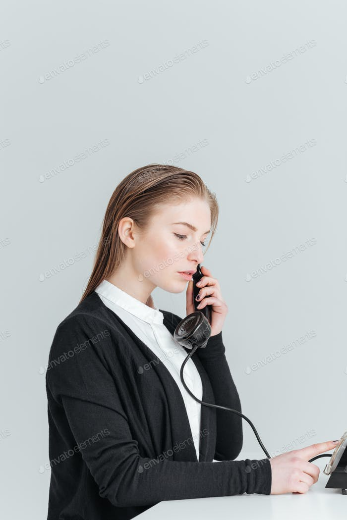 Young businesswoman talkign on retro phone