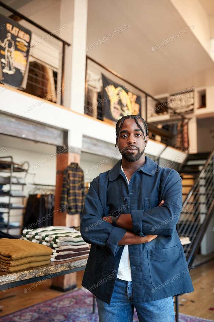 Portrait Of Male Owner Of Fashion Store Standing In Front Of Clothing Display