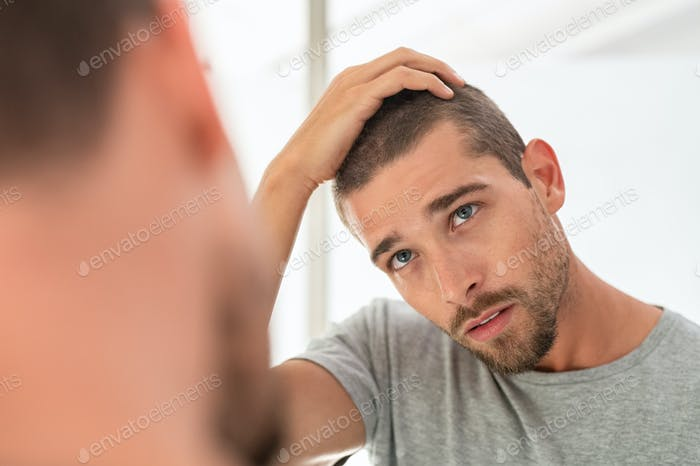 Young man checking hair in mirror