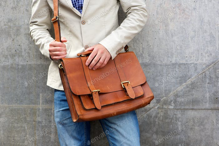 Man with leather shoulder bag standing wall
