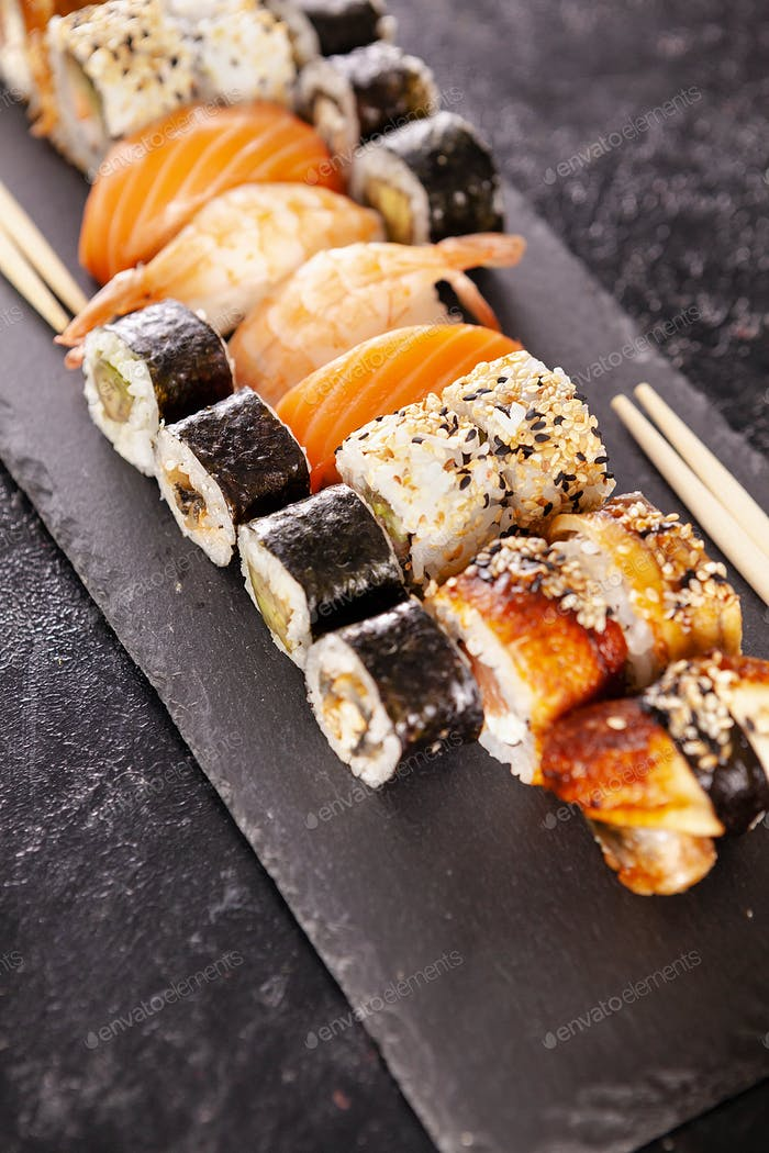 Plate with variety of sushi on a dark stone