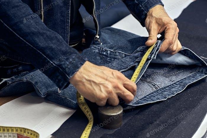 Zugeschnittenes Bild von Schneider macht Messungen von Jeans mit einem Meter in der Nähwerkstatt.