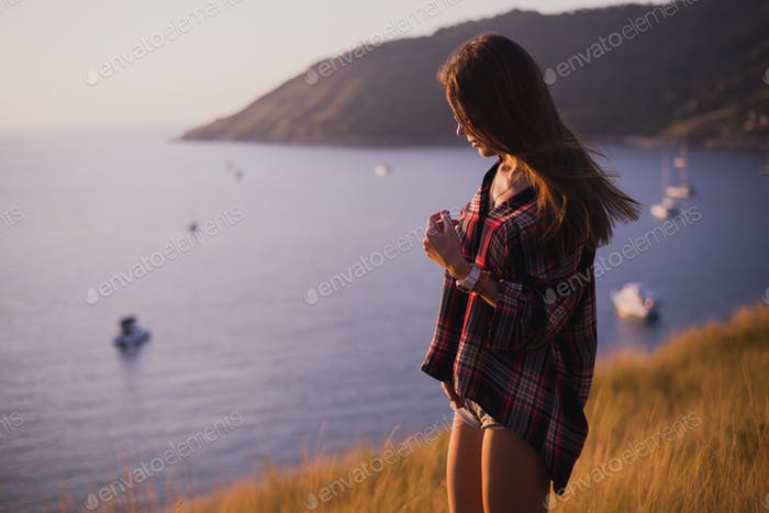 A girl stands on the edge of the cliff near the sea or ocean and looking at the sun valley. Woman