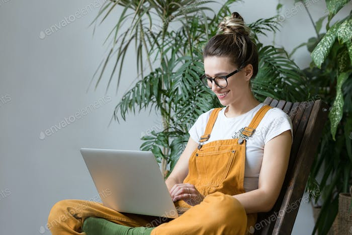 Smiling woman freelancer remote working on laptop computer at home greenhouse. Plant on background.