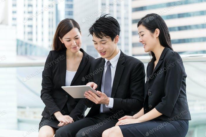 Business teammate use of digital tablet together