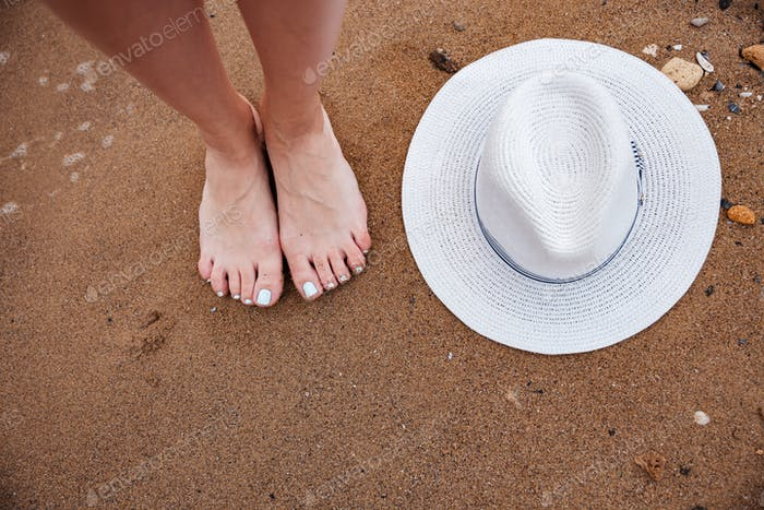 Barefoot woman legs and hat on the beach