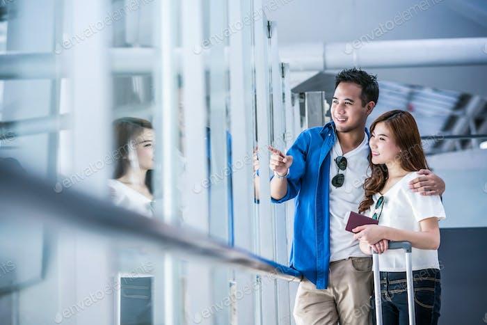 Viajero pareja asiática con el pasaporte con maletas en el aeropuerto. Viaje amante