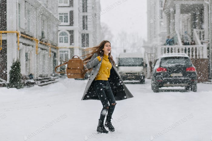 Adorable lady with brown backpack dancing on the street in winter town. Elegant young woman with lea
