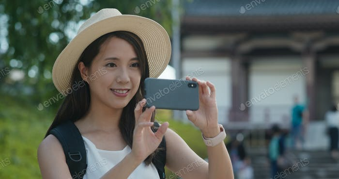 Woman travel in Japan, take photo on mobile phone in the Japanese temple