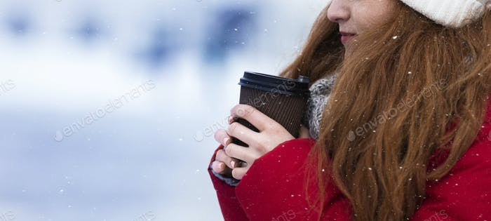 Cropped of young woman holding cup with hot drink