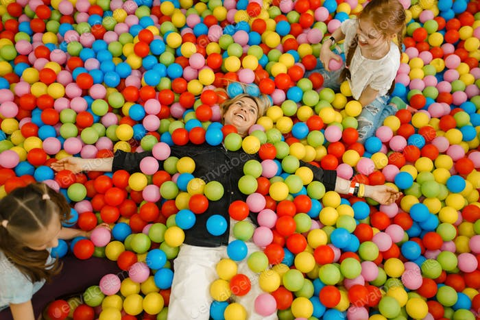 Children with mother lying among colorful balls