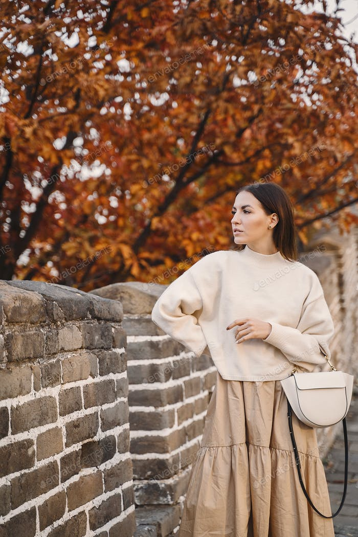 stylish girl visiting the Great Wall of China near Beijing during autumn