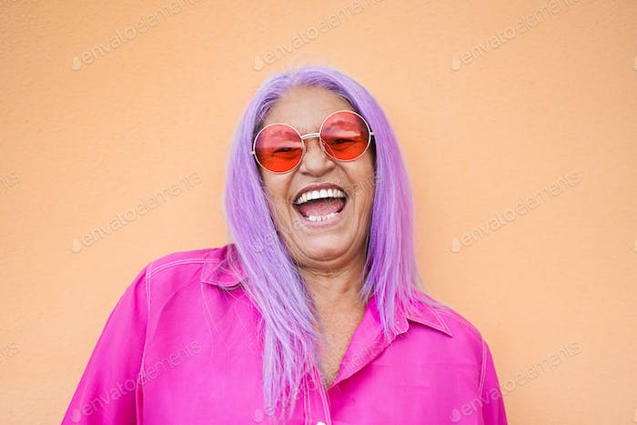 Happy senior woman laughing while wearing sunglasses - Crazy old woman with purple hairs